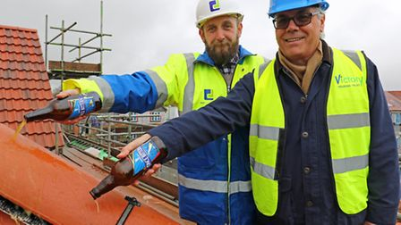 Richard Dove of builders Dove Jeffrey (left) and Darryl Cox of Victory Housing Trust top out the new