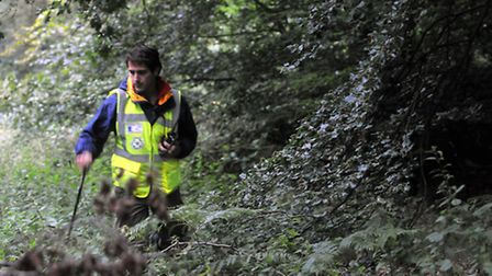 One of the Norfolk Lowland Search and Rescue team members, Neil Coston, searches the undergrowth dur