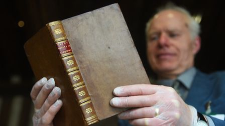 Curator Oliver Bone with a rare French edition of Thomas Paine's book, Rights of Man, which has been