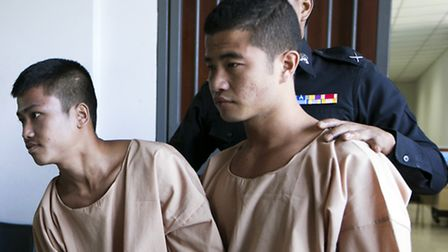 Myanmar migrants Win Zaw Htun, right, and Zaw Lin, left, both 22, are escorted by officials after th