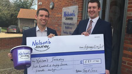 Simon Thompson of Arthur Jary and Sons Ltd presents a cheque to Simon Wright, CEO of Nelson's Journe