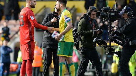 Norwich City captain Russell Martin and Ipswich Town goalkeeper Bartosz Bialkowski share a moment fo