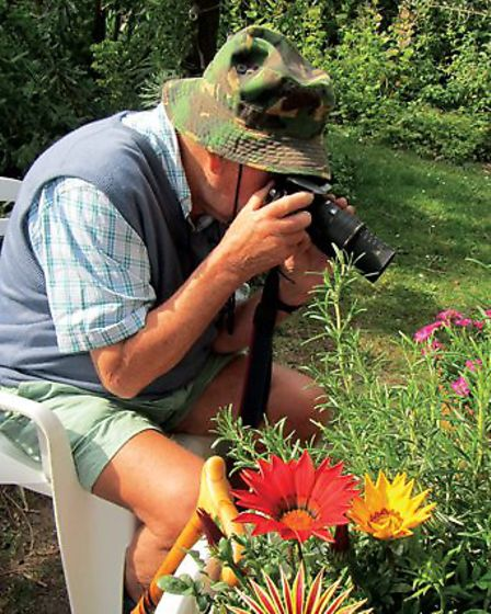 Peter Clarke at home in his garden at Holme photographing a bee, in June 2011. Picture: Vivien Clark