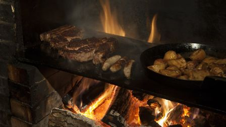 A rib of beef and venison sausages cooking on the Elk Room fire at The Gunton Arms, Cromer Road,Thor