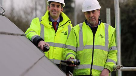 Paul Legrice (left) and Alan Read of Abel Homes perform the traditional topping out ceremony at The