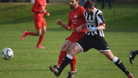 Action from Acle United (black/white) against Harleston Town. Nathan Page for Harleston against Ian