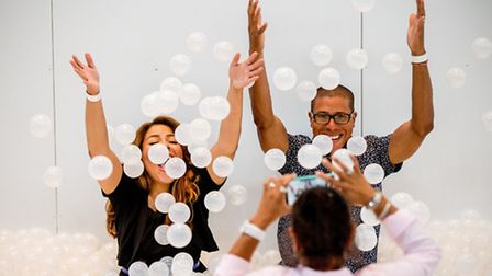Visitors to a ball pit throw plastic balls in the air as they pose for a photo. Picture: AP/Andrew H