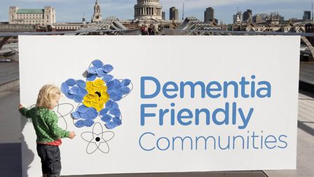 One-year-old Ivy Ames adds a message to a campaign billboard in London to encourage the Alzheimer's