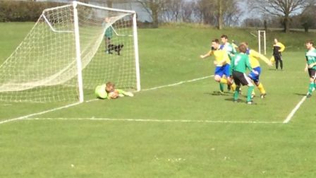 Action from the top of the table clash in the Premier Division between Acle Rangers (yellow) and DE