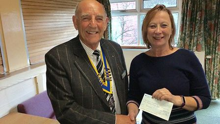Eric Craske, President of the Rotary Club of Holt and District, presents Bev Townsend of BOOM! Young