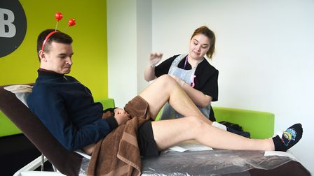 College of West Anglia student Morgan Barker having his legs waxed by Megan Simpkins on Red Nose Day