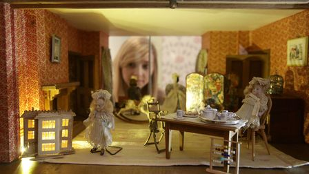Looking through a window of one of the dolls houses that is part of Small Stories exhibition at Norw