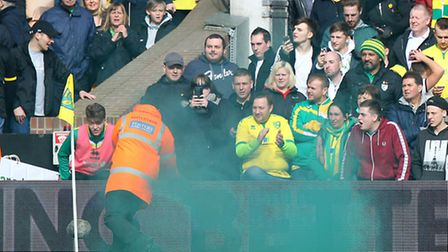 7. A steward removes a flare during the Sky Bet Championship match at Carrow Road, Norwich. Picture