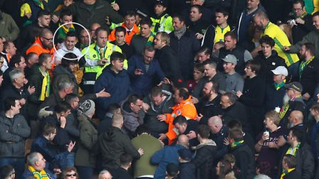 3. Stewards continue to lead Wells (circled) away following a flare throwing incident. Norwich. Pict