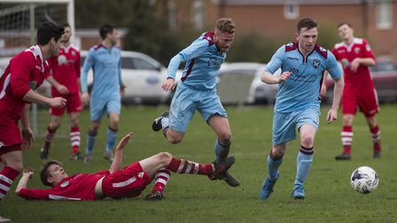 Anglian Combination football action between Spixworth (blue) and Stalham (red) . Scott Sell in the t