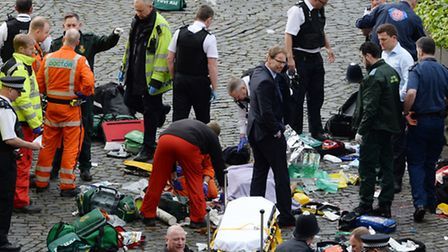 Conservative MP Tobias Ellwood (centre) stands amongst the emergency services at the scene outside t