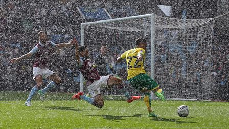 Jacob Murphy tries to get a cross in under pressure from Neil Taylor during a torrential downpour. P