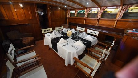 The dining table laid for dinner in the saloon, with the named directors chairs, on the 90-year-old