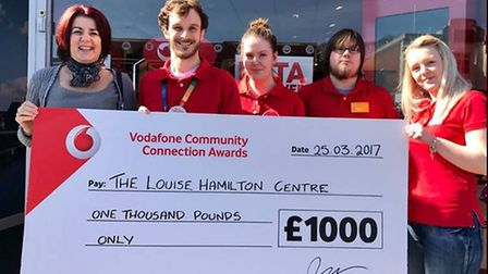 A Louise Hamilton Centre representative is presented with a cheque by Vodafone staff. Picture: Ideas