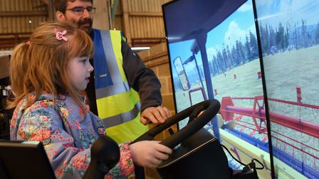 Megan Whiting, seven, tries out the combine driving simulator with help from Robert von Grabler Croz