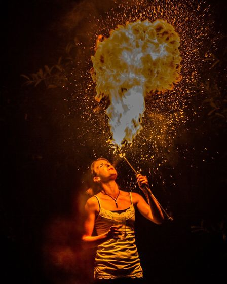 Penny Miracle, also known as Pyro Penny, eating fire. Photo by Mark Barley