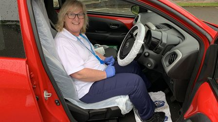 Community support worker Juliet Wilson in a car which has its own PPE