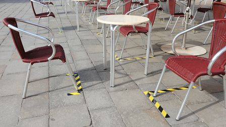 Signs on the ground to space the tables and chairs of an outdoor cafe