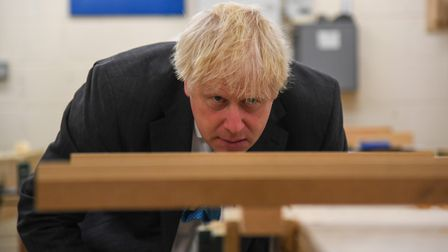 Prime Minister Boris Johnson looks at a piece of wood in a vice during a visit to Exeter College. Th