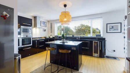 The kitchen has a matching range of wall and base units in gloss black with granite worktop over