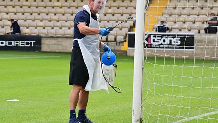 Staff spraying the corner flags with disinfectant before the pre-season match between Torquay United