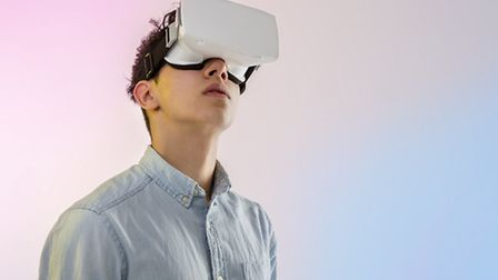 Young man wearing virtual reality headset looking up