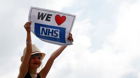 A young girl holds a We heart NHS sign in the crowds during the The Lewisham and Greenwich NHS Choir