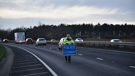 PC Amy Lucas putting out signs to warn of a broken down lorry blocking one lane of the A11. Picture: