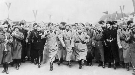 Premiere Benito Mussolini doing the goose step, Germany's ceremonial military march, which he procla