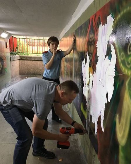 Chief Inspector Paul Wheatley and police cadets removing the vandalised graffiti boards from the und