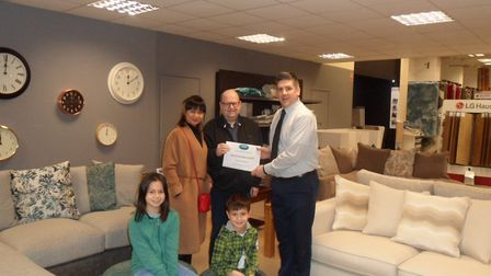 John Williams and his wife receiving their £500 voucher from Brian Weir, Cosy Carpets assistant stor