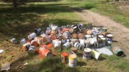 Paint tins discarded close to fire route four in Thetford Forest. Picture: Michael Annear