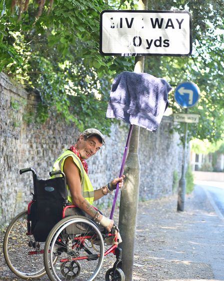Michael Read who is cleaning road signs for 24 hours to raise money to help him continue with his wo