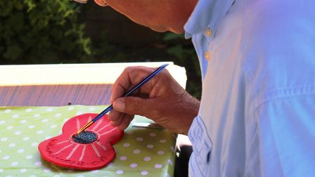 A man painting a poppy for a Remembrance Day project. Picture: Tony Parsfield