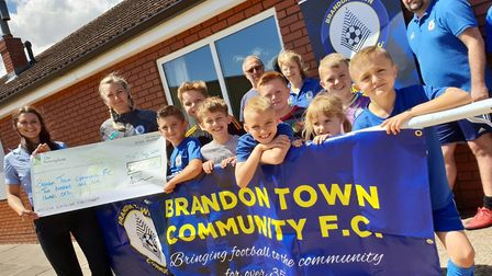 Players and coaches from Brandon Town Community FC receive the cheque from The Nottingham's customer