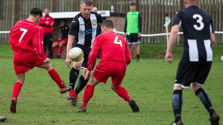 Swaffham Town Reserves'' Liam Forshaw takes on two Acle Reserves defenders during his side's big win