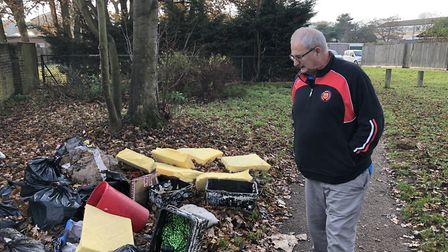 Councillor Chris Harvey looks at the dumped rubbish in Abbey Estate, Thetford. Picture: Terry Jermy