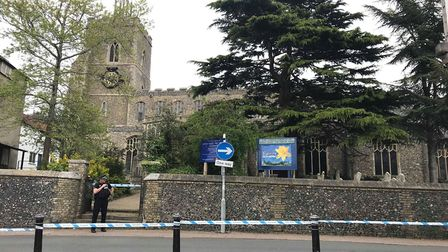 A police officer stands at the scene at St Mary's Church yard in Diss after a body was found. Photo: