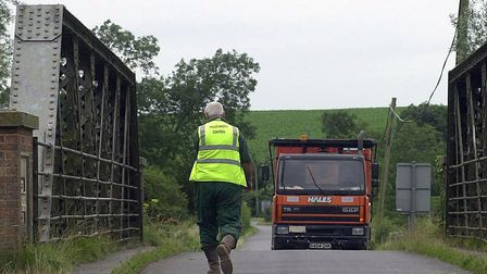A lorry driver heads back to his vehicle after walking across a bridge to ask residents for directio