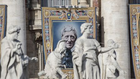 A tapestry portraying Cardinal John Henry Newman hangs from the facade of St. Peter's Basilica, at t