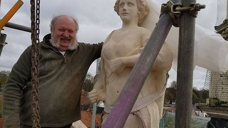 A replica of Thetford's statue of justice has been returned to its home on top of the Guildhall, mad