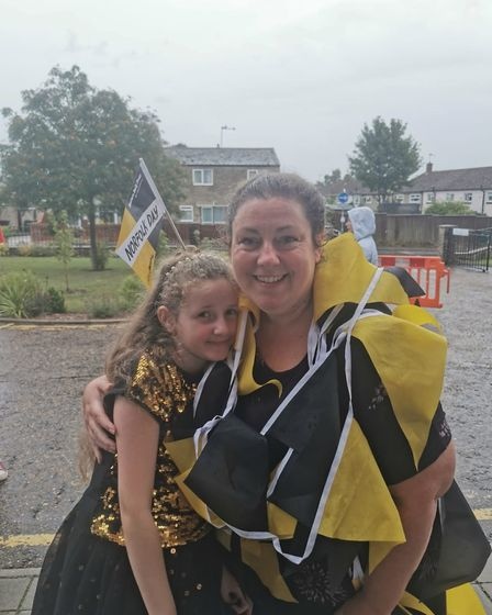 Billie Lawler wrapped up in Norfolk Day bunting with her daughter Erin at the Norfolk Day event at t