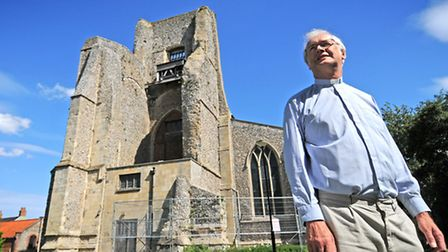 Canon Derek Earis pictured with the crumbling tower of St Nicholas Church, North Walsham.PHOTO: ANTO