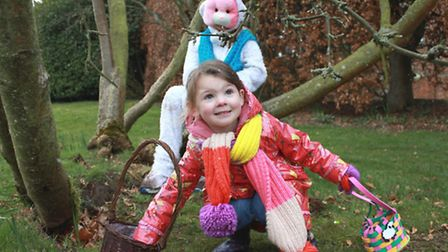 Three-year-old Grace Rhodes finds chocolate eggs left by Easter bunny Maisie Moxon, 10, during a pre
