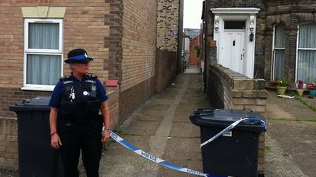 An officer stands guard at the alleyway linking Crown Road and Albion Road